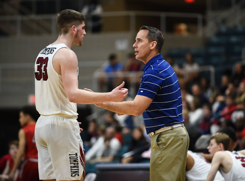 Tompkins coach Bobby Sanders and his son, senior forward Hank Sanders (33), have a discussion during the Falcons' Class 6A regional quarterfinal playoff game against Bellaire on March 3 at the Merrell Center.