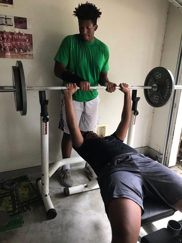 Brothers Aaron and Zach Session, offensive linemen at Morton Ranch High, lift weights together at their home.