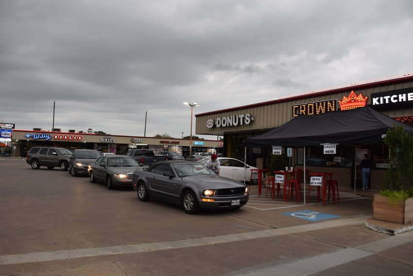Crown Kitchen diners line up to pick up their food orders. Colburn McClelland, owner of Crown Kitchen and Willy Burger in downtown Katy, said Crown Kitchen is feeding thousands and working to help keep morale up in town.