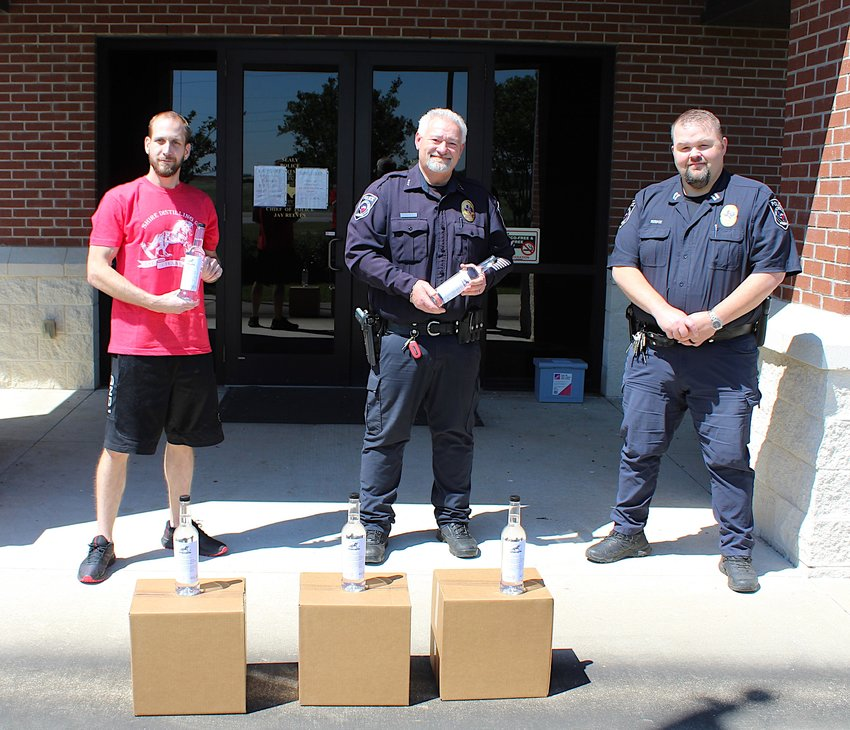 Tim Raines, co-founder and master distiller of Shire Distillery, dropped off two boxes of hand sanitizer to the Sealy Police Department and Chief Jay Reeves (center) and Captain Scott Riske (right). The distilling company out of Brookshire recently transitioned from whiskeys and vodkas to hand sanitizer.