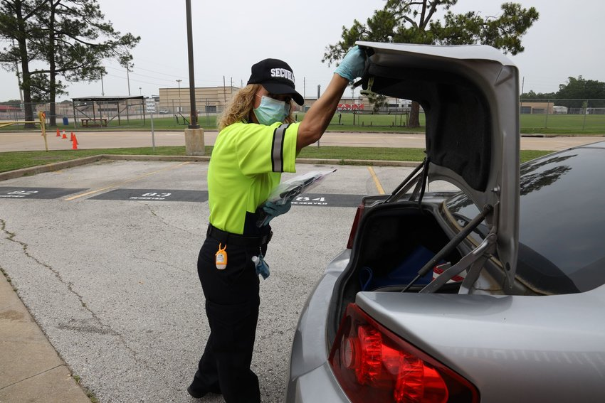 A variety of Katy ISD personnel pitched in for the drive-thru distribution of internet-capable devices April 22 at the Katy ISD Education Support Complex. Delivery was contactless with staff placing sanitized, prepackaged devices in the trunks of families picking up devices.
