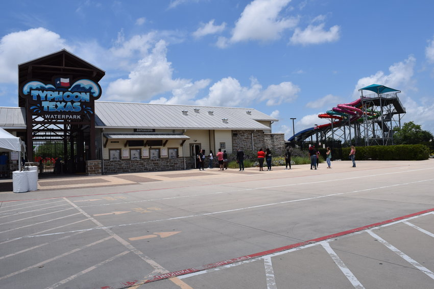 Customers wait in line to purchase tickets Thursday morning so they can get access to Typhoon Texas over the summer season. The local water park, which features several water slides and a lazy river, has instituted safety measures which meet the requirement of Gov. Greg Abbott's current executive order allowing Texas to open back up.