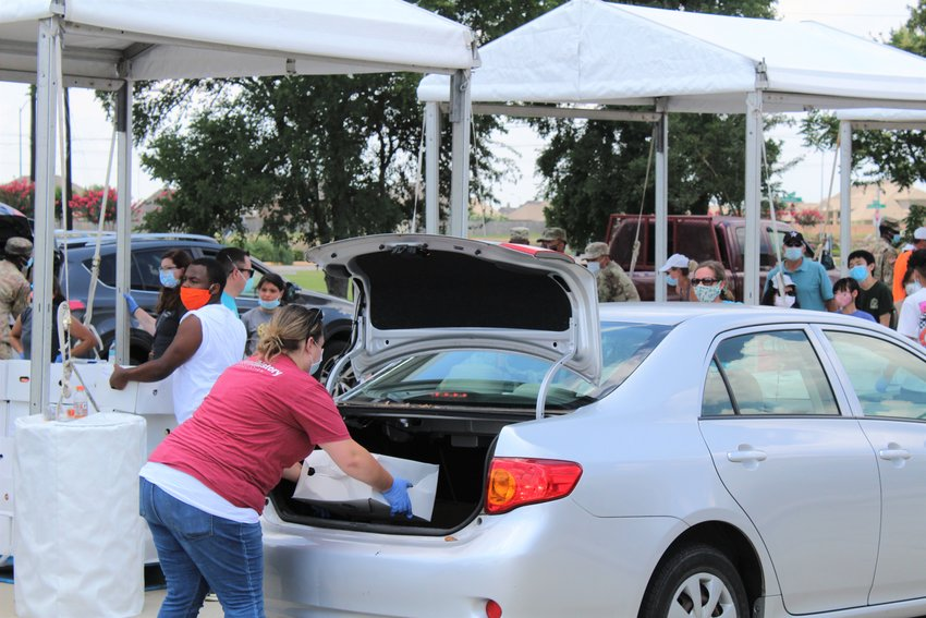A volunteer places a food box inside the trunk of a car to limit contact and stop the spread of COVID19 at a Houston Food Bank distribution site on June 2.