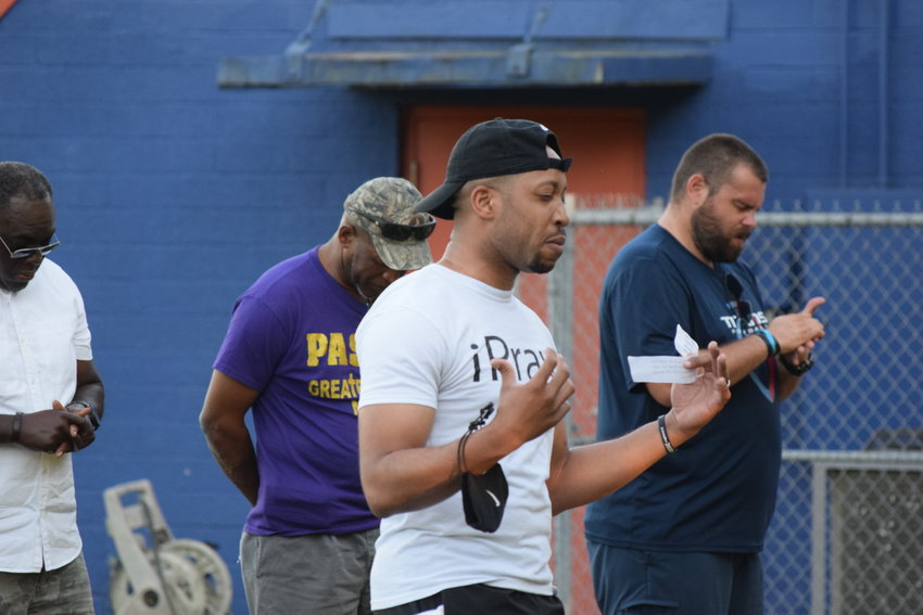 A Brookshire area resident gives a prayer at the praytest event. People of several racial and cultural backgrounds joined in the event.