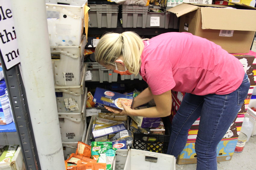 A volunteer organizes recently acquired food supplies at the Katy Christian Ministries food bank during the store's mid-afternoon closure, allowing for restocking.