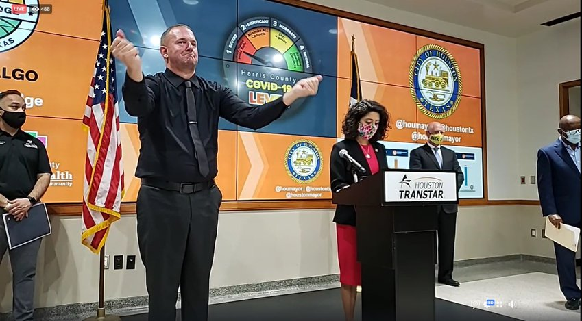 Harris County Judge Lina Hidalgo leads the press conference announcing the delay of in-person instruction for Harris County schools. The man in all black provides interpretation in American Sign Language which utilizes facial expressions.