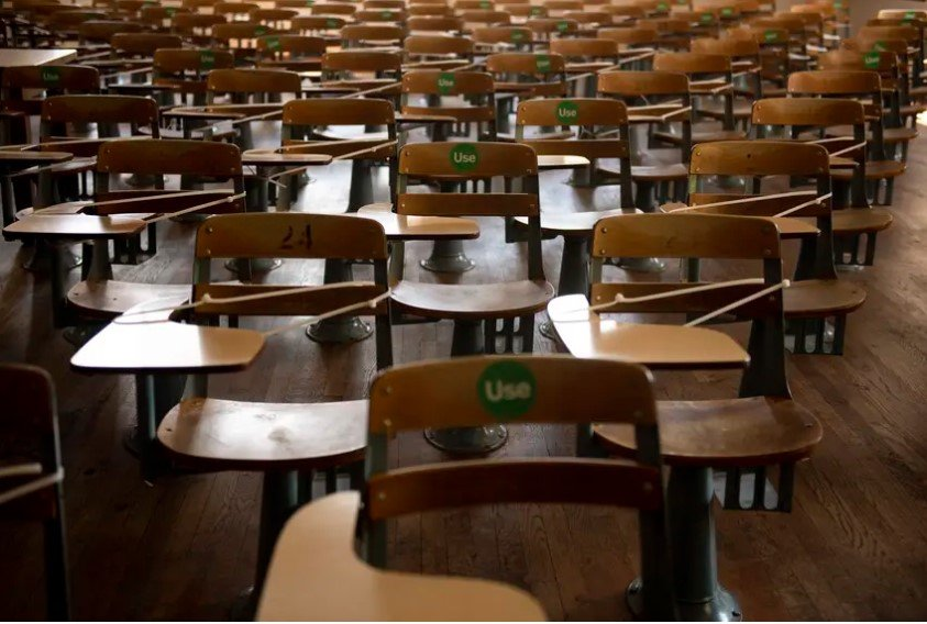 "Desks are zip-tied and a green ""Use"" sticker is placed on available desks to practice social distancing in an academic hall at the University of Texas at Austin on Aug. 24, 2020."