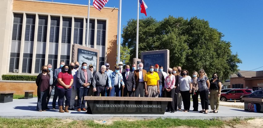 Members of the Waller County Commissioners Court and community members who helped bring the new Waller County Veterans Memorial to fruition pose for a photo in front of the new monument to the contributions of veterans.
