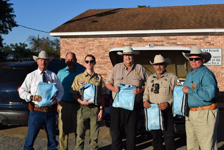 Seth Reid (third from left) poses with his father (blue polo shirt), Waller County Precinct 4 Constable Joel Trimm (center), deputy constables and officers from the Waller County Sheriff's Office. The bags being held up are care packages for young children that may need comforting when dealing with stressful situations law enforcement becomes involved in. Reid created the care packages as part of his work toward becoming an Eagle Scout.