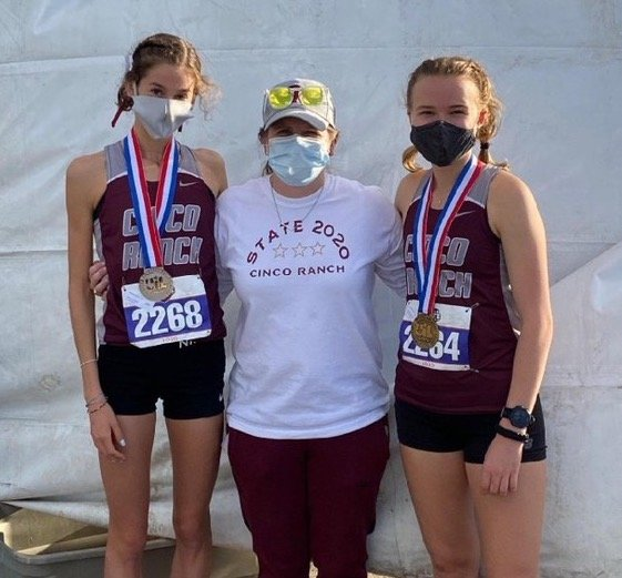 Cinco Ranch seniors Sophie Atkinson, left, and Heidi Nielson, right, pose with coach Dana Mathis after finishing second and third, respectively, at the UIL Class 6A state meet on Tuesday afternoon in Round Rock.