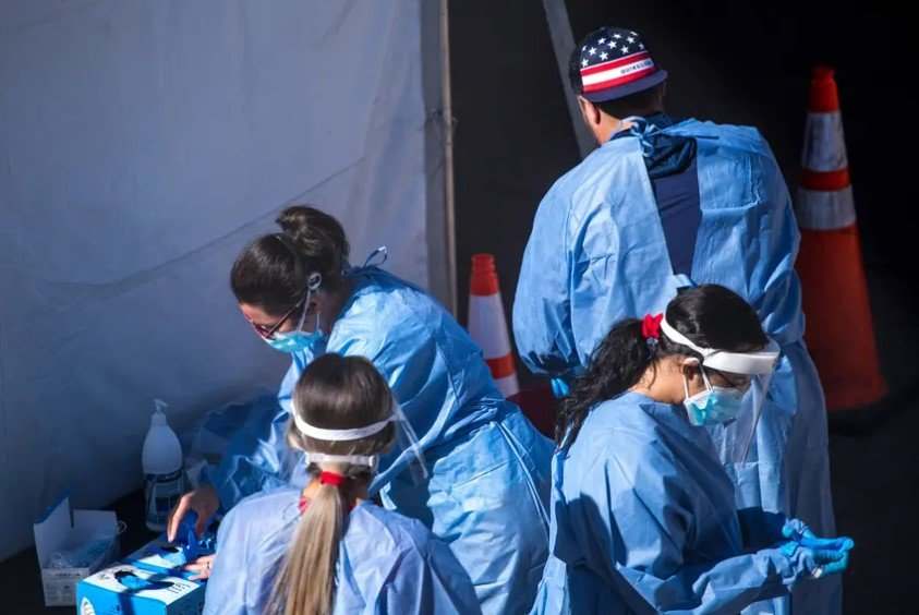 Medical personnel put on personal protective equipment at a COVID-19 testing site at the University of Texas at El Paso on Nov. 3. Heading into the Thanksgiving holiday, Texas has set new records for the number of people testing positive for the coronavirus.