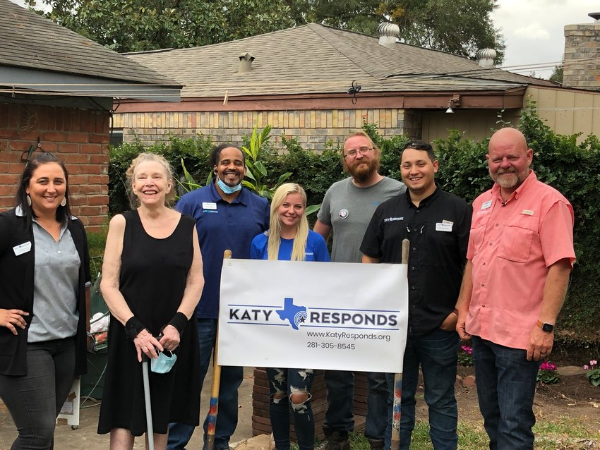 Katy Responds volunteers and staff pose with Virginia Holcomb (second from left). Holcomb's home was flooded and became Katy Responds' 100th home to be repaired. The organization repairs homes impacted by disasters such as floods, but also works with those experiencing family emergencies such as single mothers who need assistance making home repairs.