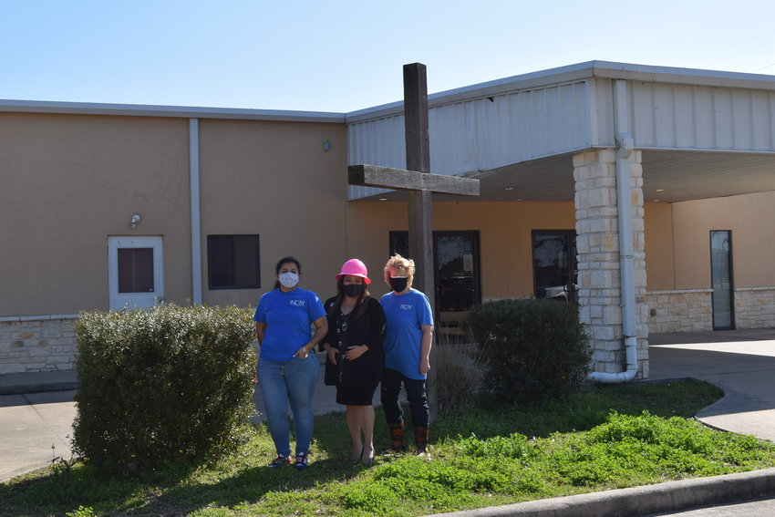 Katy Christian Ministries Executive Director Deysi Crespo (center in pink hardhat) poses with KCM Business Development Manager Jeannette Trejo (left) and KCM Master Gardener Karen Smith (right) in front of KCM's new headquarters building at 3506 Porter Road in the Katy area. The new facility will allow the nonprofit to consolidate operations, enlarge its food pantry and enhance its community garden.