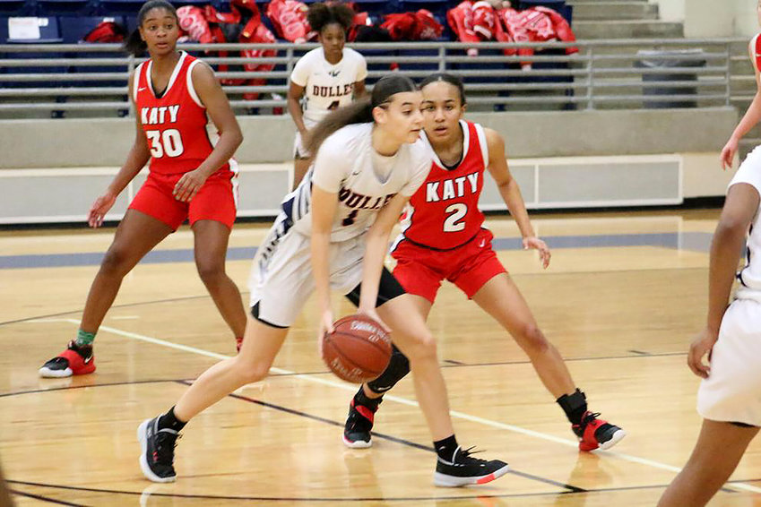 Dulles junior guard Dai Dai Powell moves the ball as she is guarded by Katy senior guard Amber Bourgeois in Thursday's 6A bi-district playoff game at Hopson Field House.
