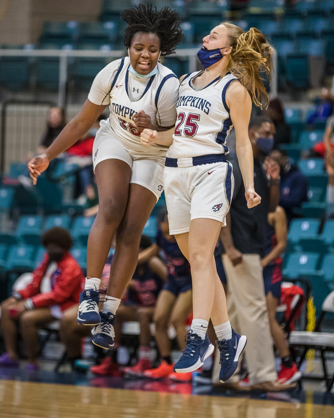Tompkins' teammates Fiyin Adeleye (35), left, and Kennedy Bourque (25) celebrate at mid-court following the Falcons' win over Fort Bend Dulles in Wednesday's Region III Class 6A quarterfinals at the Merrell Center in Katy.