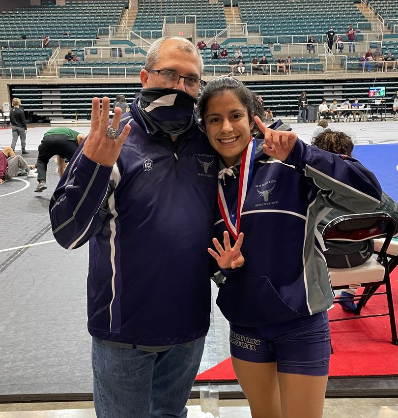 Morton Ranch senior Brittany Cotter poses for a congratulatory photo with coach Mark Balser after Cotter won her fourth district championship at the 9-6A wrestling tournament Saturday, April 10. Cotter is the first Maverick wrestler to win a district title all four years of her high school career.