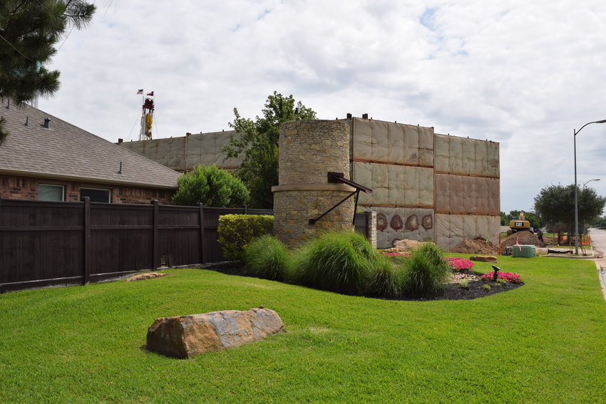 Katy&rsquo市最新的水井附近的房屋之间立着一个消声屏障。钻探引起了对噪音的担忧和经常发生的房屋震动,导致附近的居民抱怨这种情况。凯蒂市议会已经批准增设隔音屏障,以减轻该项目造成的困扰。
