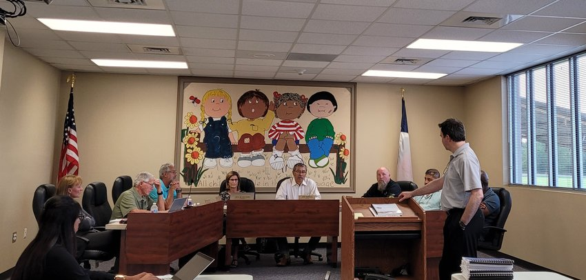 Chris Brown (at podium) addresses Pattison City Council during Tuesday evening's meeting – the first in-person meeting for the city's governing body since the pandemic forced them to go remote. Council met at the Royal ISD Administration Building, but may soon have their own council chambers to hold meetings in. Pictured from left to right: Deputy City Secretary Andrea Govea, City Secretary Lorene Hartfiel, Council Member Robert MacCallum, Council Member Wayne Kircher, City Attorney Lora Lenzsch, Mayor Joe Garcia, Council Member Seth Stokes, Council Member Frank Cobio, Jr. and Council Member Fred Branch (behind Brown).