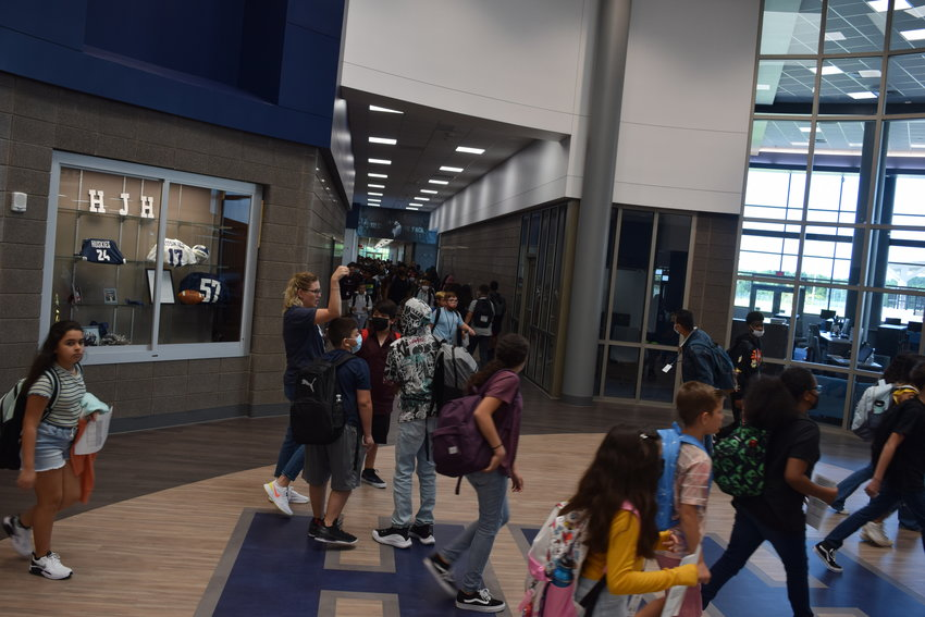 Students move between classes in the span between first and second period at Haskett Junior High School. Many of the students and staff wore masks, but not all.