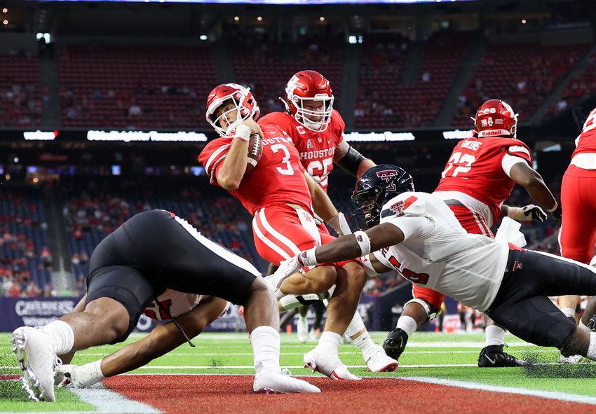 Houston Cougars quarterback Clayton Tune (3) escapes the grasp of Texas Tech Red Raiders linebacker Riko Jeffers (6) in the end zone to avoid a safety during an NCAA football game between Houston and Texas Tech on September 4, 2021 in Houston, Texas.