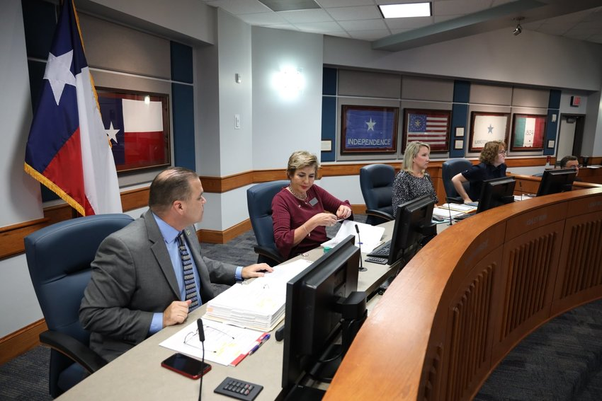 Dawn Champagne (second from left in maroon) speaks with Katy ISD Superintendent Ken Gregorski (far left) during a recent Katy ISD Board of Trustees meeting.
