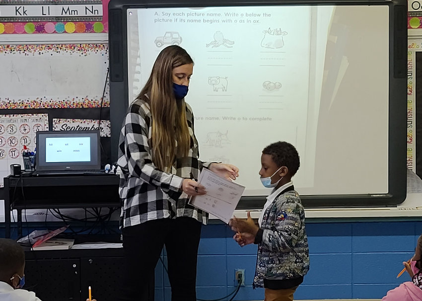 Kemper County Lower Elementary School teacher Ms. Abby Watson works with Ayden Boyd in her first grade students earlier this month. School in the Kemper County district is session and students are back in the class room.