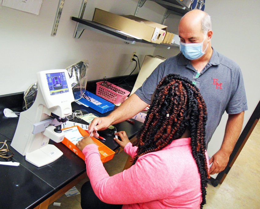 EMCC Ophthalmic Technology instructor Eddie Sciple works with students on the Scooba campus earlier this semester. The school has announced registration for its upcoming semesters.