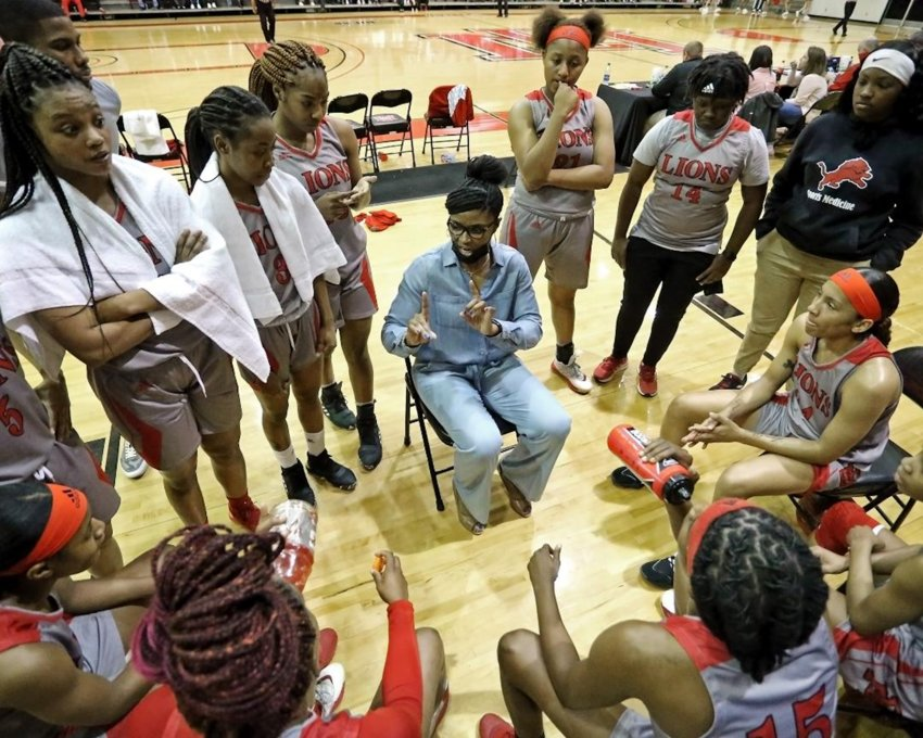 Coach Sharon Thompson's East Mississippi Lady Lions listen up during a timeout in an earlier game. In the other photo, Ja'Mia Hollings takes a shot in an earlier game. The Lady Lions were 12-4 when they played Coahoma in the semifinals Wednesday at Mississippi College.