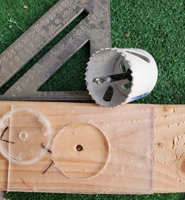 Creating arm holes in the COVIDBox prototype with a saw made by NMSU students