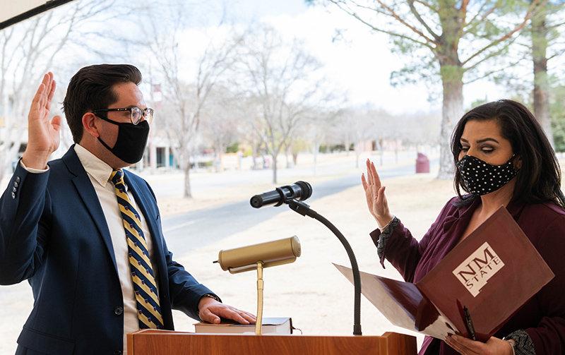 Neal Bitsie is sworn in as the NMSU Student Regent by Doña Ana County Clerk Amanda López Askin, Wednesday March 24, 2021. (NMSU photo by Josh Bachman)