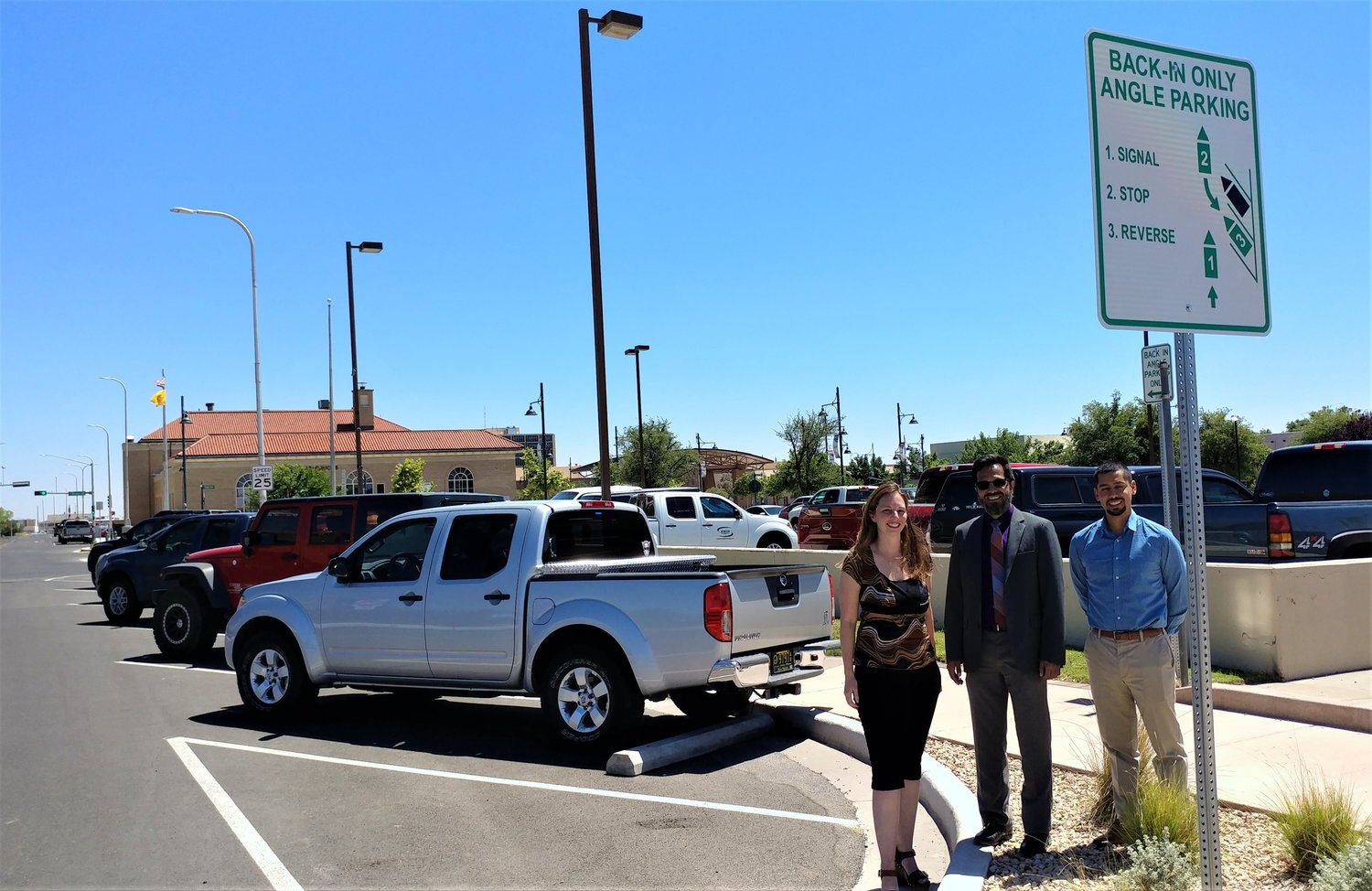 With vehicles correctly parked in the City of Las Cruces' new back-in angle parking spaces on Church and Water streets are, left to right, city Economic Development Administrator Mandy Guss, Public Works Department Director David Maestas and Economic Development Specialist Armando Morales. The sign above them, and similar signs all along Church and Water streets, explains the three-step, back-in parking process. (Bulletin photo by Mike Cook)