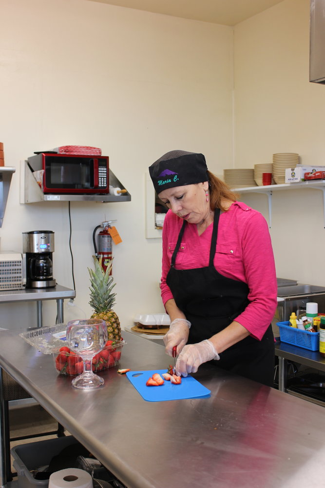 Maria Chavez Vento, co-owner of the new restaurant Mari Boquitas Café and More, cuts fresh strawberries for a Frescas con Crema.