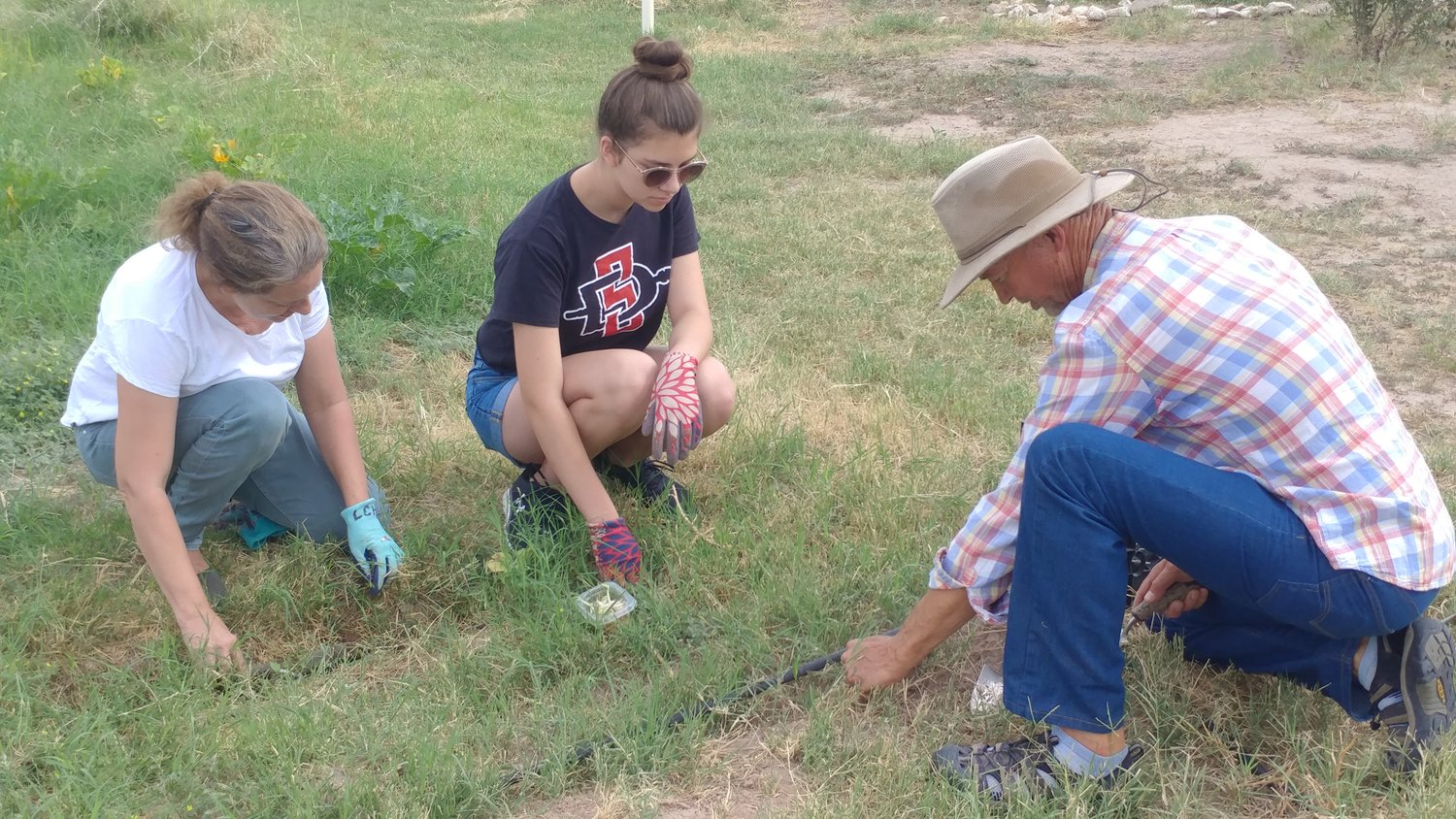 Urban garden volunteers Gina Marquez, left, and Lily Marquez planting seeds with Doña Ana Soil and Water Conservation District Supervisor Craig Fenske.