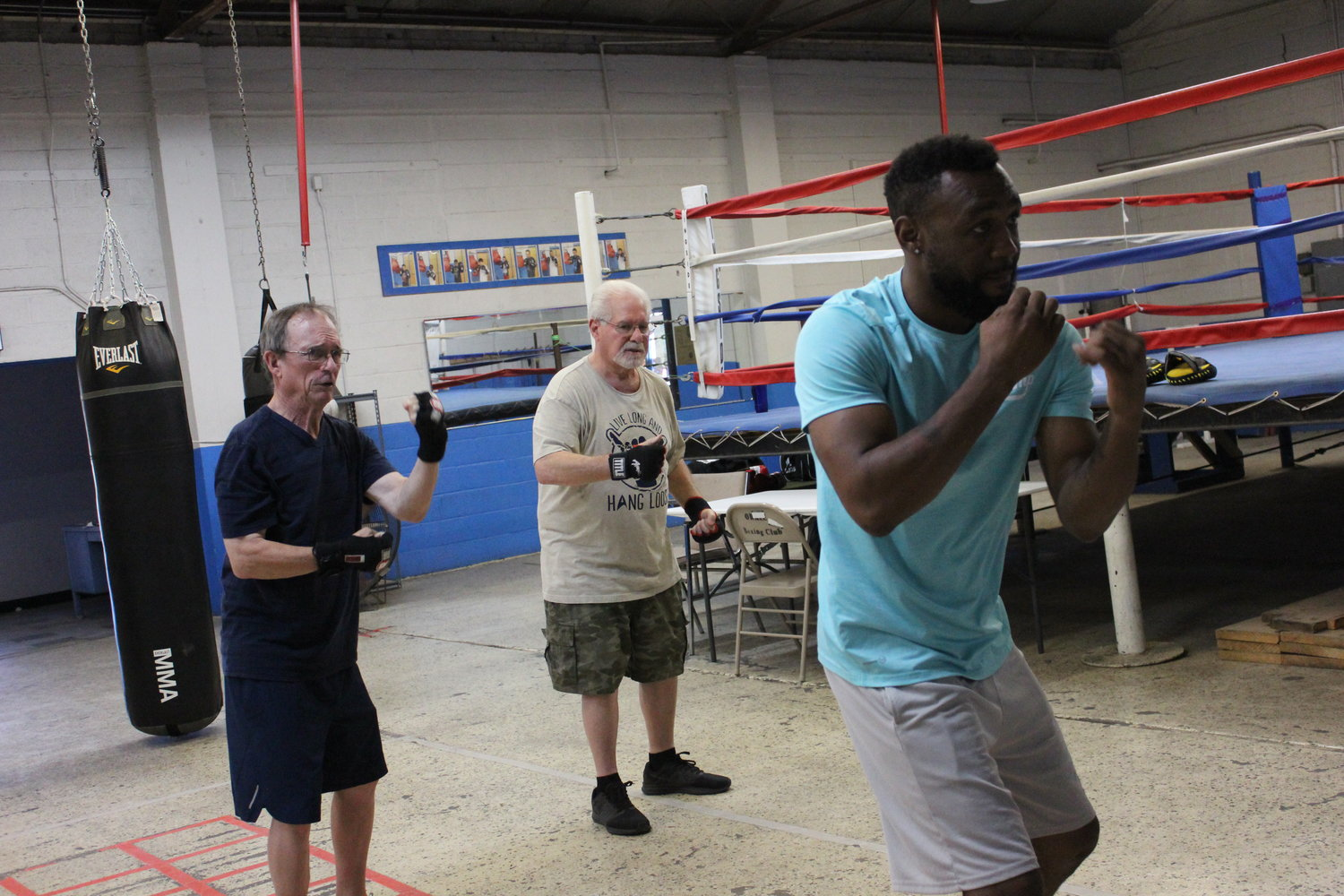 Austin Trout leads Bob Skolnick, right, and Jon Roberts, left, through various punching combinations during a Rock Steady Boxing class on Friday, Aug. 2.