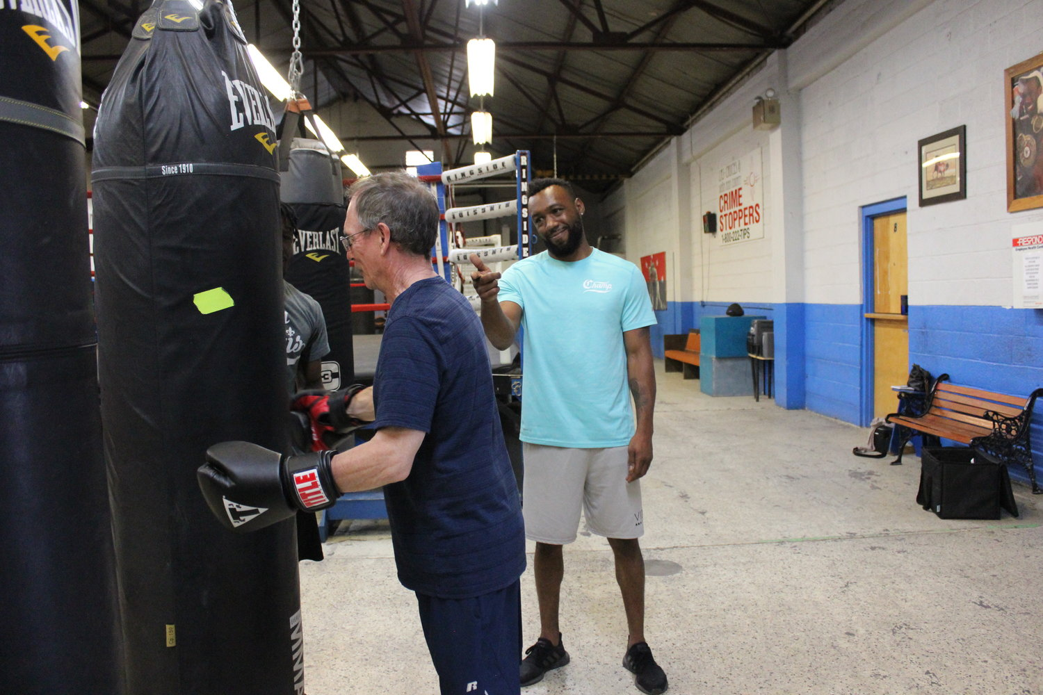 Austin Trout helps guide and encourage Jon Roberts, left, as he hits the bag in a Rock Steady Boxing class held at Las Cruces PAL Boxing, 700 N. Solano Drive.