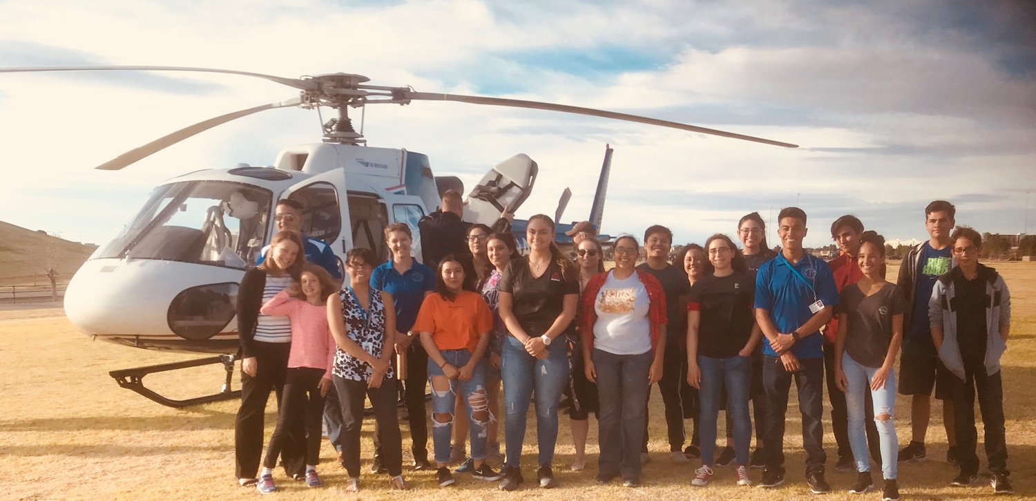 Program leaders and students in the Youth Medical Explorers Program pose for a photo during a hospital helicopter activity.