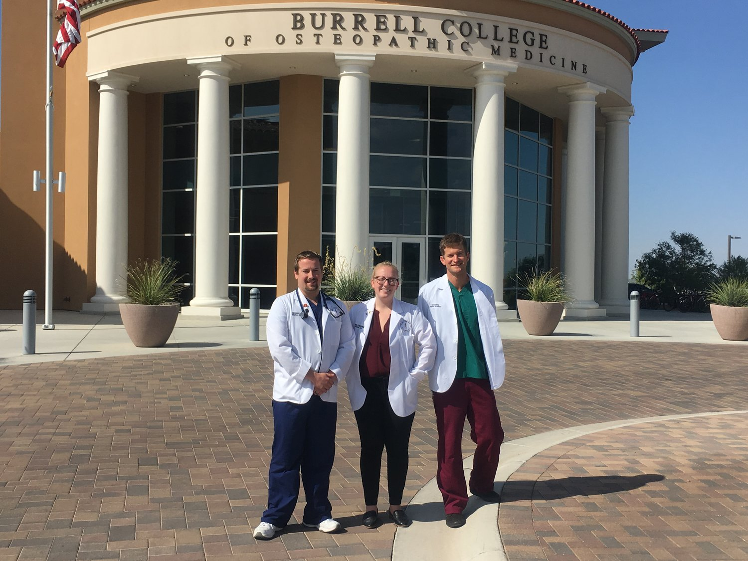 From left, Youth Medical Explorers Program Co-Chairs Nicholas Chajec, Virgina Stoddard-Merriam and Lee Boyle stand outside Burrell College of Osteopathic Medicine, located on the New Mexico State University campus.