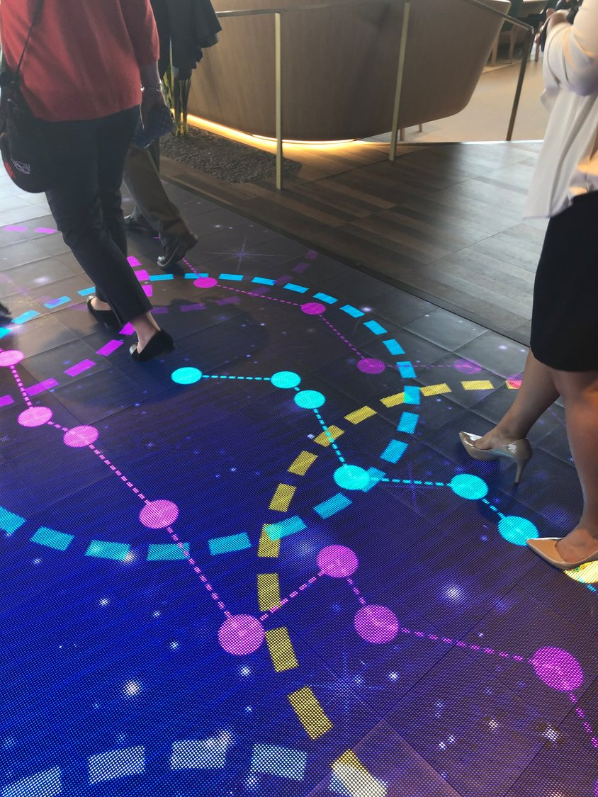 An interactive walkway lights up with circles and footsteps under guests as people enter the lounge area from the Gateway to Space hangar and take in the New Mexico vista of mountains and runway.