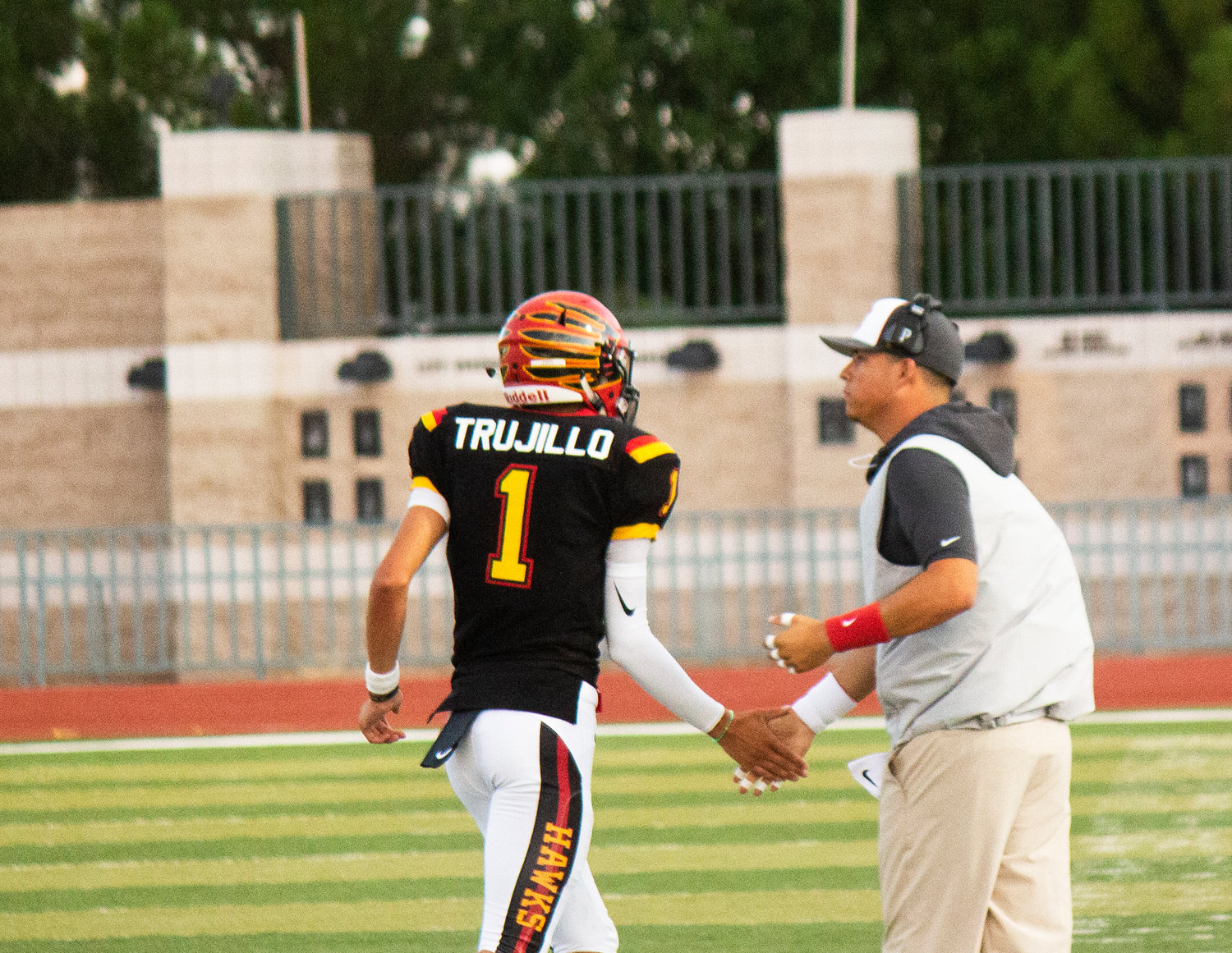 Quarterback Aiden Trujillo gets props from offensive line coach Matthew Flores.