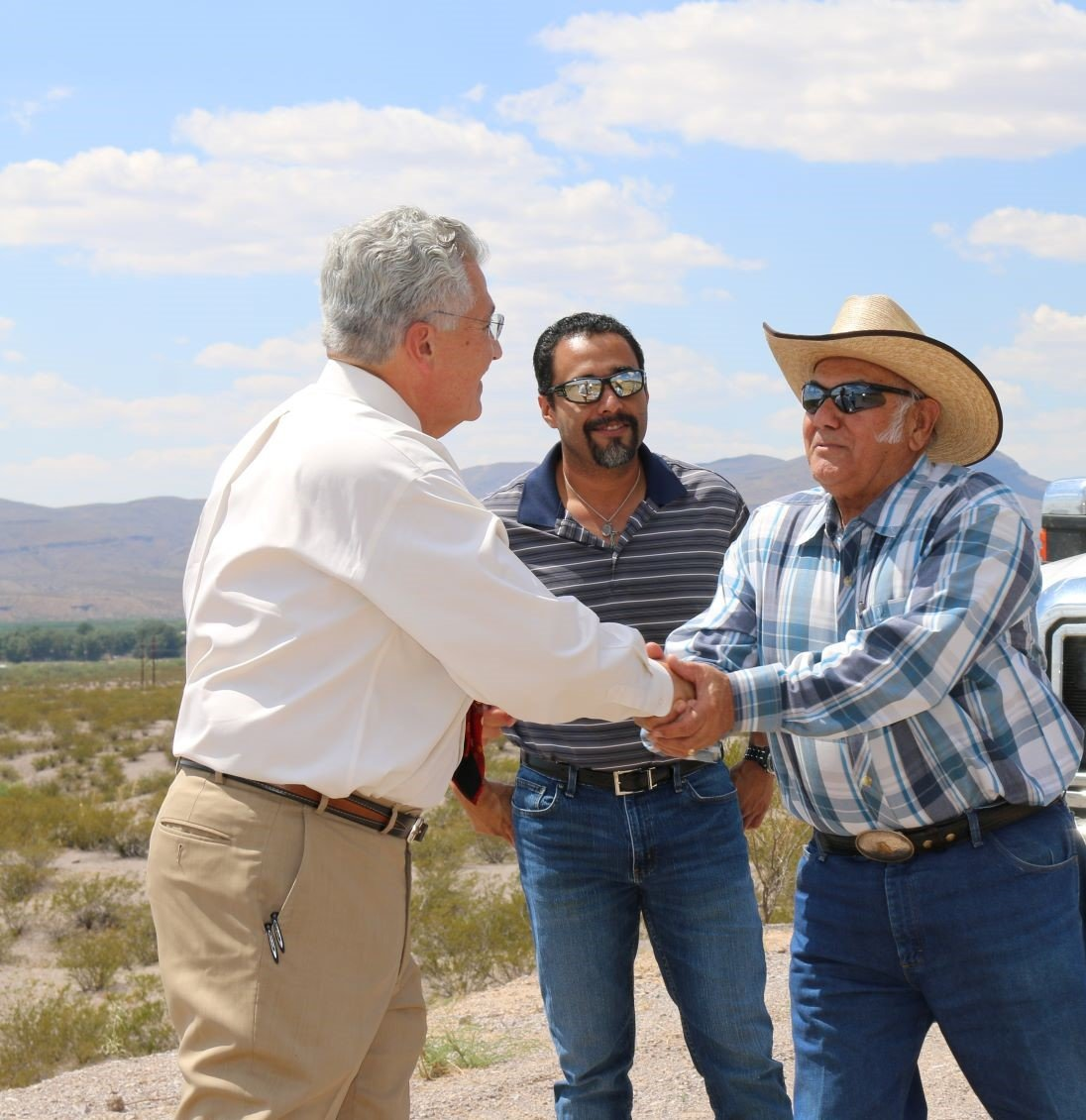 From left, Doña Ana County Manager Fernando Macias and Andrew Guerra, supervisor engineer with the Flood Commission, meet farm owner David Alvillar.