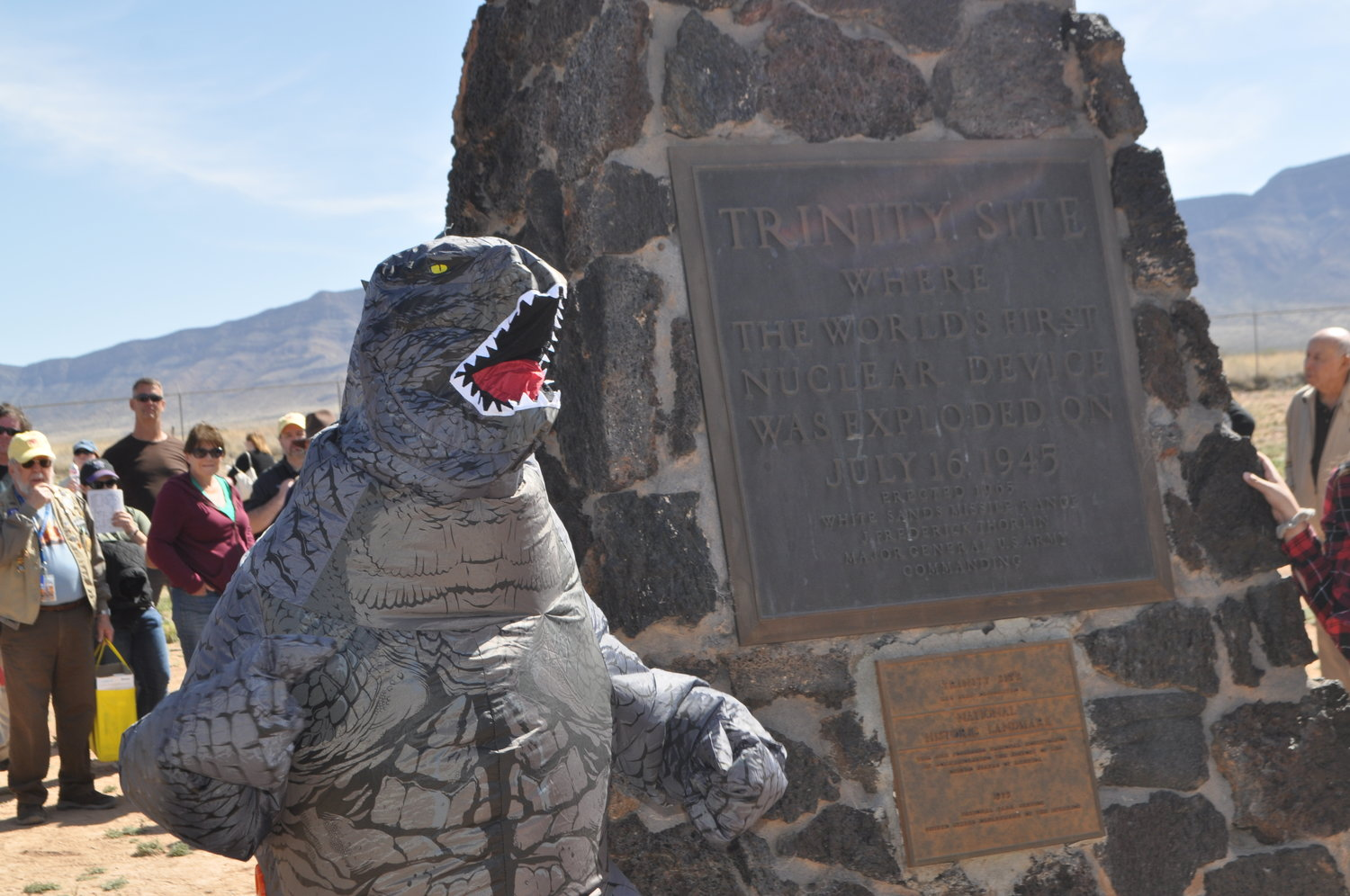 Godzilla hangs out at the Trinity Test site challenging visitors who have come to read the plaque on the black obelisk commemorating the test.