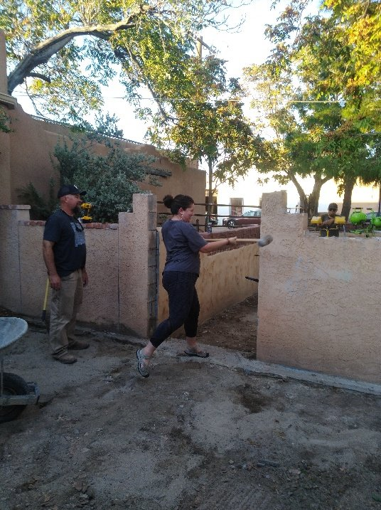 NM Vintage Wines co-owner Morgan Switzer-McGinley takes a hammer to the wall of the old patio, so construction on the expanded patio can begin.