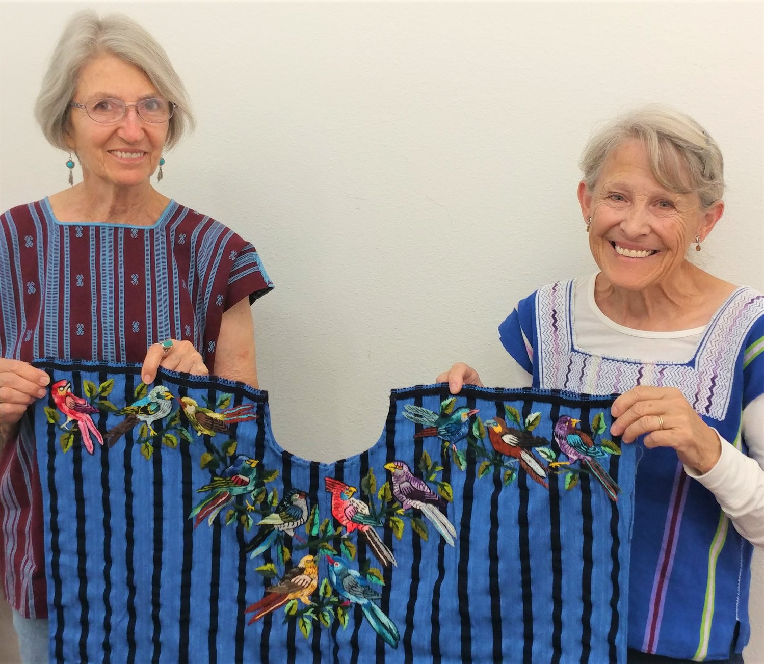 Textile Sale to Benefit Maya Youth co-coordinators Janet Darrow and Christine Eber are wearing and holding Maya textiles.