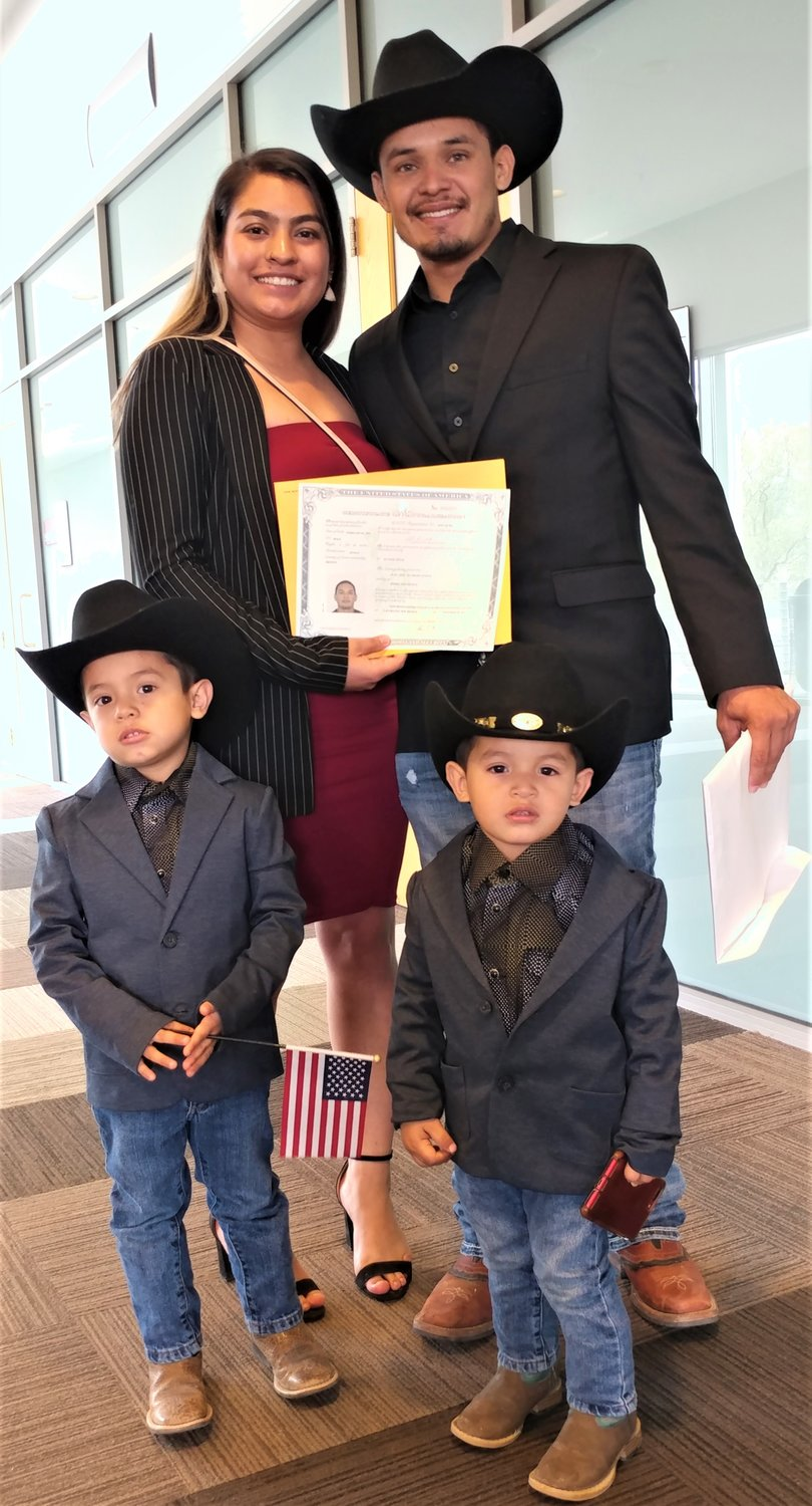 Juan Jose Alvarado became a U.S. citizen during swearing-in ceremonies. Joining him for the service were his wife, Chantal, and their sons, Nicolas, 3, holding the American flag, and Josiah, 2, holding the cell phone.