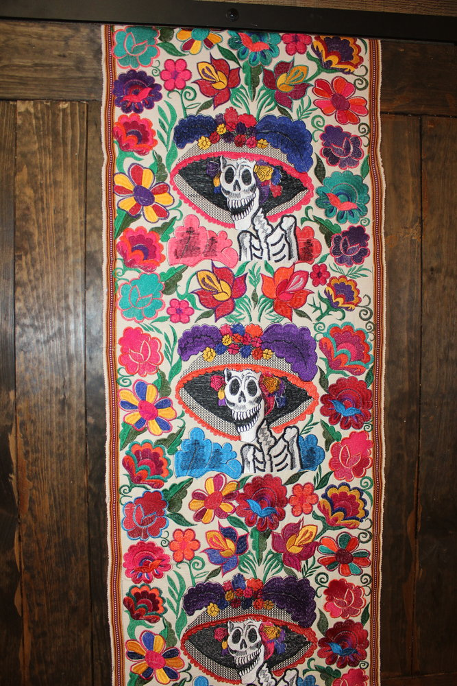 A tapestry featuring art based on Jose Guadalupe Posada's original Catrina La Calavera Garbancera, is one of many pieces of art adding to the color and vibe of Taqueria Las Catrinas.