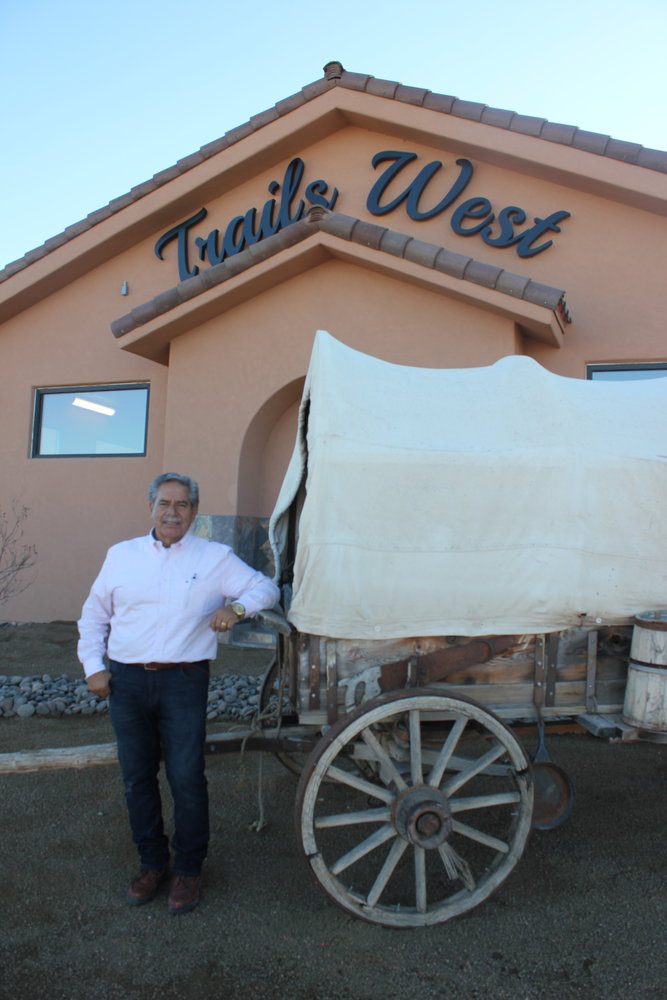 Ruben Zamora, who manages the grounds at Trails West, poses with a decorative covered wagon that accents the community's second clubhouse.