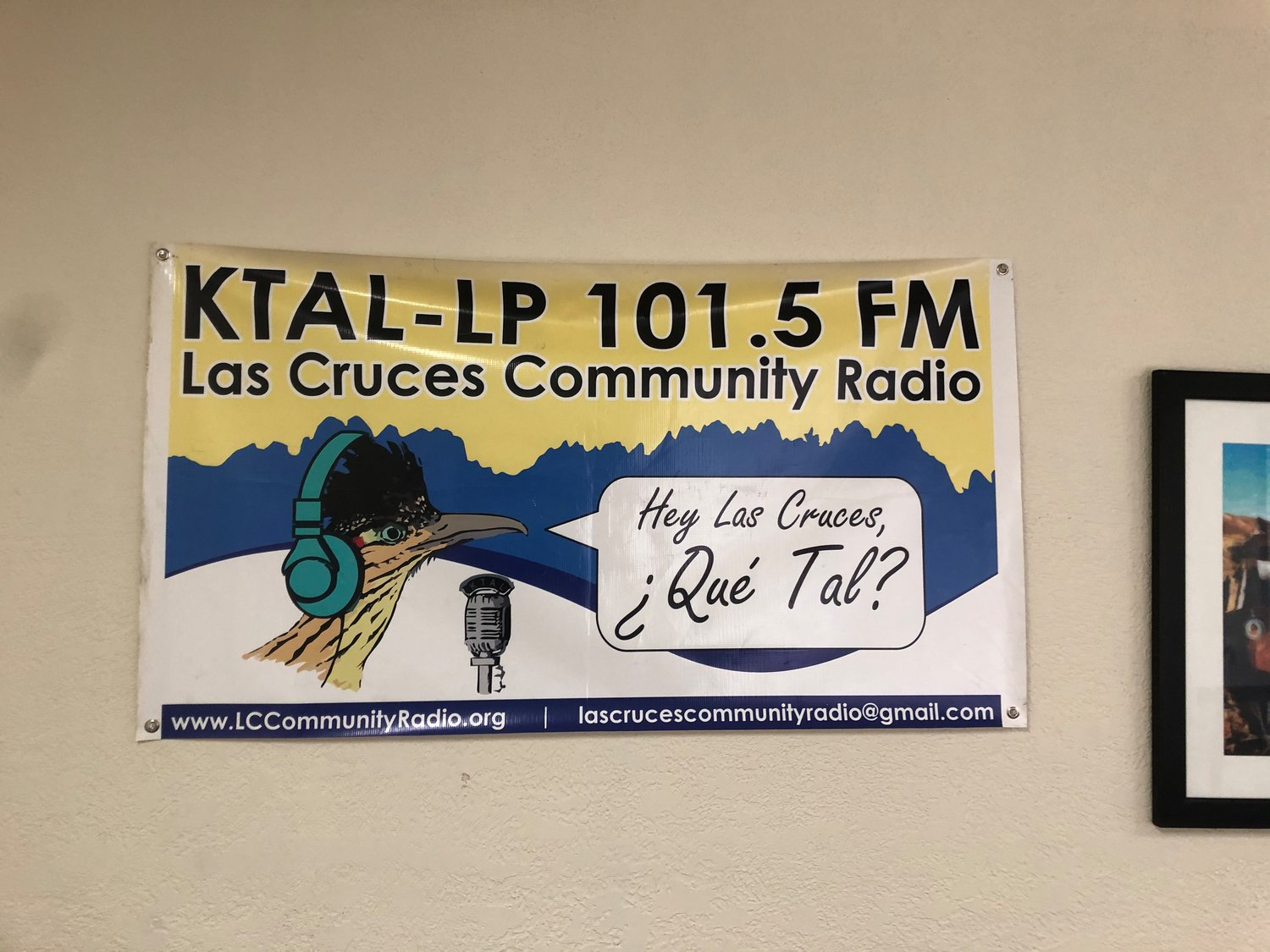 The KTAl-LP banner at the studio asking Las Cruces what's up (¿Qué Tal?).