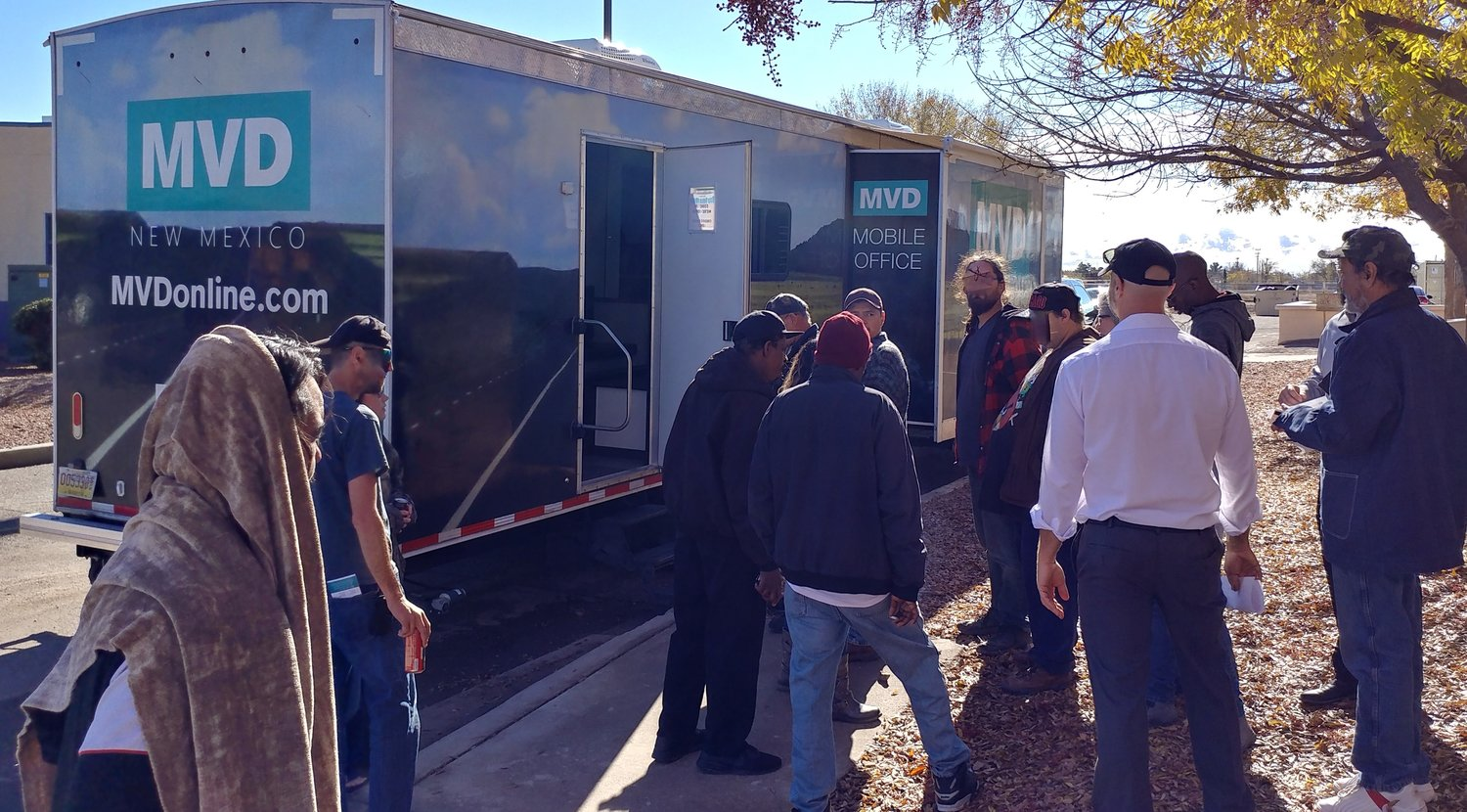 Clients of Mesilla Valley Community of Hope (MVCH) and residents of its Camp Hope Tent City line up for services at the state Motor Vehicle Department mobile unit to get IDs Friday, Nov. 22, at MVCH. New Mexico Department of Workforce Solutions Sec. Bill McCamley, (in the white shirt) a former Las Cruces state representative and Doña Ana County commissioner, talks to participants in the event.