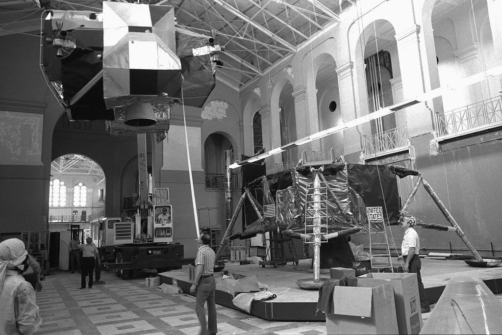 Apollo Lunar Module 2 (LM-2) is disassembled for transfer to the new National Air and Space Museum in 1975. One of Robert Goddard's New Mexico-era rockets stands in the far corner, center. Moving unique artifacts is a challenge, regardless of size.