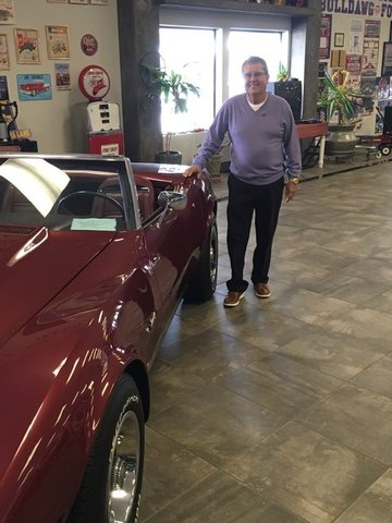 Danny Gamboa with a 1970s Corvette in his expansive showroom.